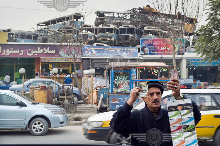 A man works on a street offering money exchanges and sells mobile phone credit. In the background is a row of shops and a scrap heap of old buses.