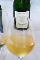 A wine glass filled with Jacquesson Avize Grand Cru Millesimee vintage 1995 on a white table cloth and a bottle in the background, Champagne Jacquesson in Dizy, Vallee de la Marne, Champagne, Marne, Ardennes, France, low light grainy grain