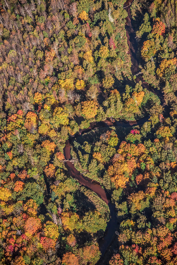 Aerial photography of a river flanked by fall color near Big Bay, Michigan.