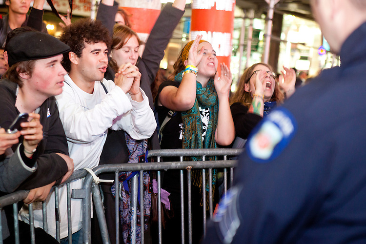 """Protesters with """"Occupy Wall Street"""", having been blocked by barricades for the better part of two hours in Times Square, thank the suddenly accomodating NYPD who decide to let them cross the street on October 15, 2011 in New York City.  While crowd estimates numbered in the tens of thousands, police tactics (including nets, motor scooters, barricades, arrests, and intimidation by riders on horseback) prevented the crowd, which had been split up, from joining together as one in the middle of Times Square.  By the time the NYPD removed some barricades and let protesters join each other their numbers had dwindled significantly as many went to a rally in Washington Square Park rather than wait in Times Square."""