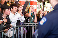 "Protesters with ""Occupy Wall Street"", having been blocked by barricades for the better part of two hours in Times Square, thank the suddenly accomodating NYPD who decide to let them cross the street on October 15, 2011 in New York City.  While crowd estimates numbered in the tens of thousands, police tactics (including nets, motor scooters, barricades, arrests, and intimidation by riders on horseback) prevented the crowd, which had been split up, from joining together as one in the middle of Times Square.  By the time the NYPD removed some barricades and let protesters join each other their numbers had dwindled significantly as many went to a rally in Washington Square Park rather than wait in Times Square."