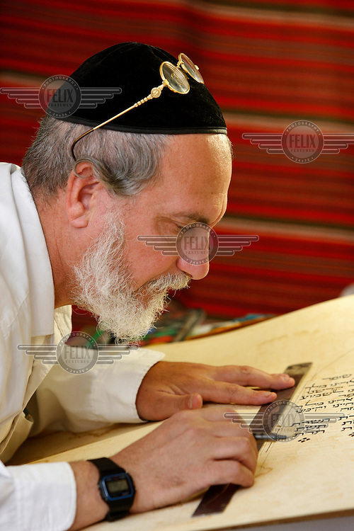 A Jewish calligraphist working on a parchment.