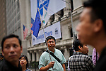 A man holds a flag as identification while he works as guide for tourist in front New York Stock Exchange. October 6, 2012. United States economy has gained 114,000 jobs, putting the jobless rate from 8.1 percent to 7.8 percent, first time it's been below 8 percent since 2009.  Photo by Eduardo Munoz Alvarez / VIEW.