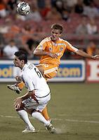Houston Dynamo midfielder Stuart Holden (22) shoots the ball over New England Revolution defender Jay Heaps (6).  New England Revolution beat Houston Dynamo 1-0 at Robertson Stadium in Houston, TX on May 19, 2007.