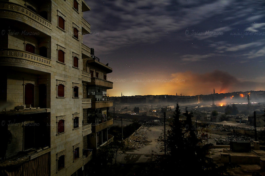 Smoke and fire (seen in the distance) rises from the Masaken Hanano and Bustan Al-Basha neighbhorhoods as fighting continues through the night. In the rebel-controlled areas of Aleppo, electricity, cellphone and internet lines have been cut for the 9th consecutive day. The Assad government claims that the rebels are responsible for the blackout. In the case of the internet, activists claim that this is technically impossible, since the Free Syria Army is not capable to cut all internet connections since most of them (three of the main fiber optic cables are located in the coastal city of Tartus), are in regime-controlled areas of Syria. As winter approaches, residents prepare for the harsh few months ahead of them...December 01, 2012...© Javier Manzano.