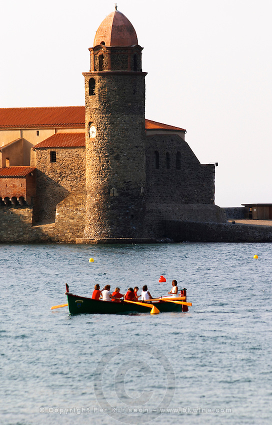 The church Eglise Notre Dame des Anges, our lady of the angels. With its emblematic church tower. A group of women practicing rowing in an old fashioned rowing boat. Collioure. Roussillon. France. Europe.