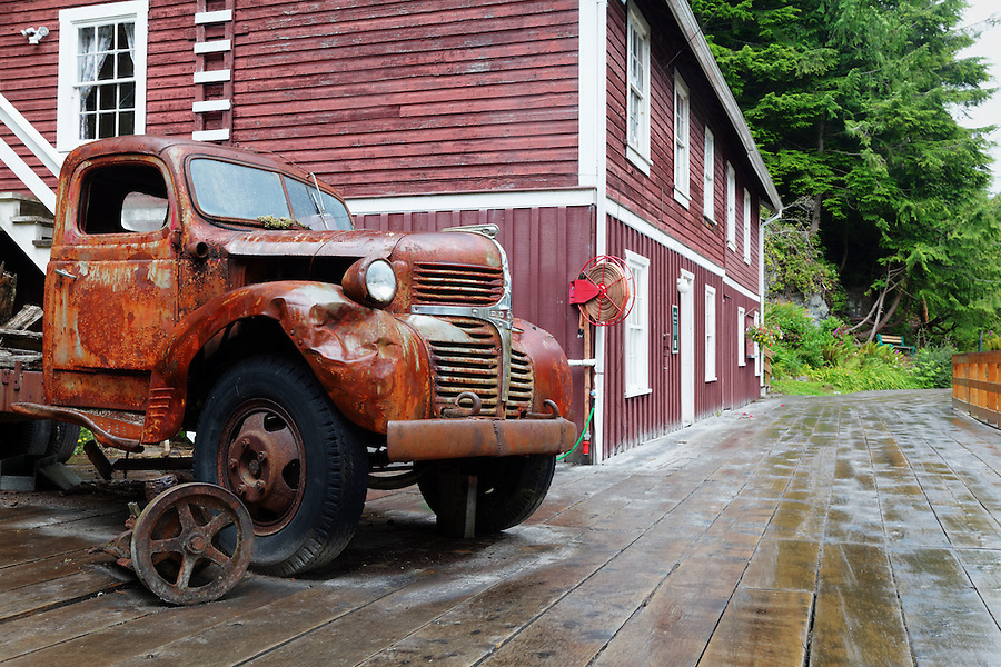 Old rusty truck parked on wharf boardwalk and shops, Telegraph Cove, Vancouver Island, Canada
