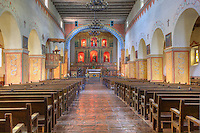 "Chapel Sanctuary with alter, pews, tile floor, adobe building at Mission San Juan Batista, a historic Spanish mission on the ""Mission Trail"" in the city of San Juan Batista, California.  Founded  1797."