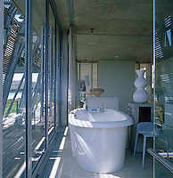 A contemporary free-standing bath in a room with glass doors and shutters which lift away to reveal views of the ocean