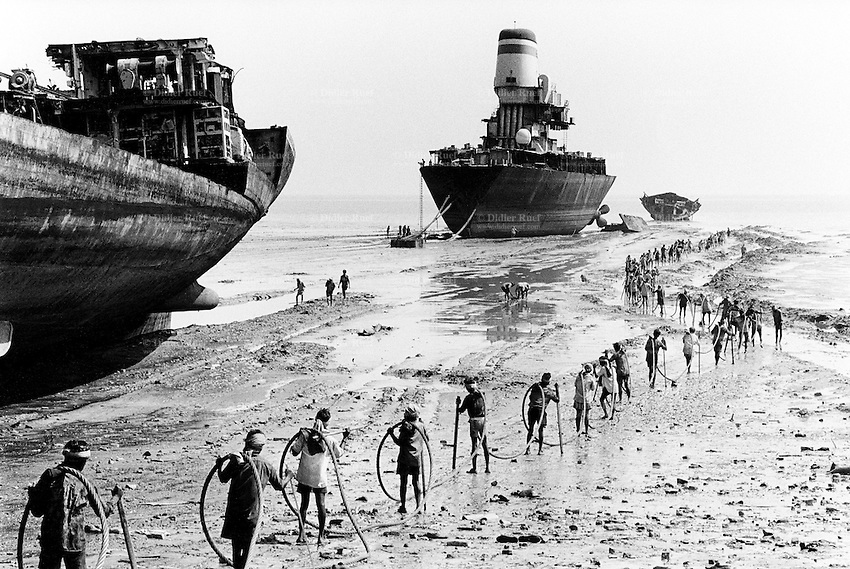 India. Province of Gujarat. Alang. Workers, all men, carry a wire to draw by winch a huge scrap's piece on the beach. Ships aground. Vessels stranded. Bottoms of ships at low tide on the shore. Alang, located in the Gulf of Khambhat, is a ships breaking place. Alang is considered as the biggest scrapyard in the world. Ships recycling for its metals. Environmental issues. Hazardous waste. © 1992 Didier Ruef