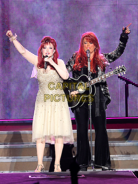 "THE JUDDS -  Naomi & Wynonna Judd.The Judd's ""The Last Encore Tour"" at the Mandalay Bay Events Center, Las Vegas, Nevada, USA,.18th December 2010..music concert gig live on stage full  length guitar black jacket playing microphone sisters group band family siblings singing gold dress  trousers arm raised up performing .CAP/ADM/MJT.© MJT/AdMedia/Capital Pictures."