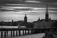 Riddarholmen i Stockholm staden vid vattnet i en svartvit siluett.
