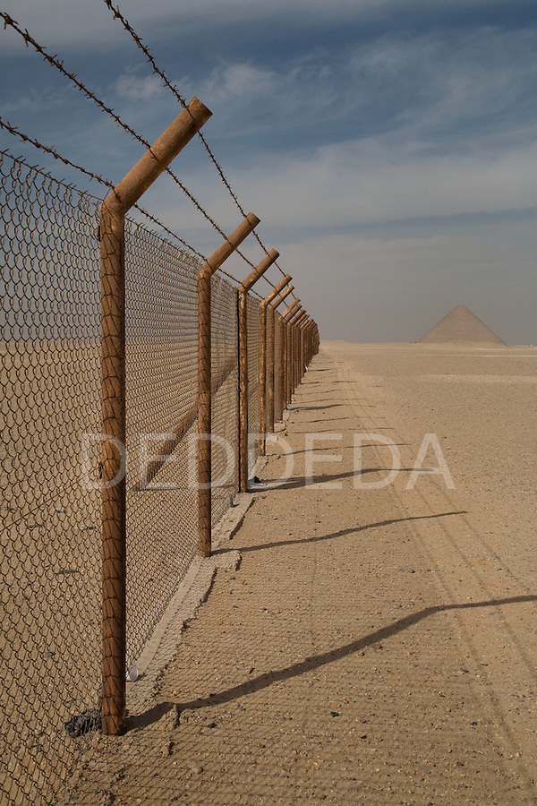 Rusty military fencing surrounds the site of the Red Pyramid, the world's oldest true pyramid, also known as the North Pyramid, located 10km south of Saqqara in Dahshur, Egypt.