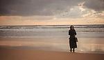 A girl stnads on the beach. Photo by Sanad Ltefa
