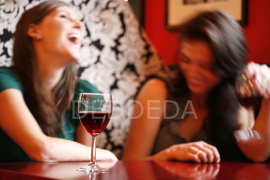 Two women laugh as they drink red wine at Bon Rouge in Victoria, BC, British Columbia, Canada. Shot for a Bon Rouge ad campaign.