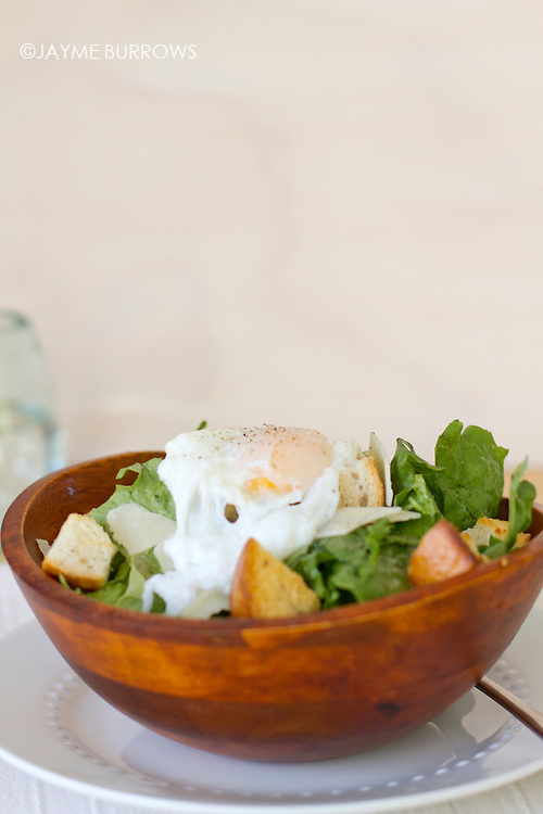Ceasar salad with a poaced egg on top.