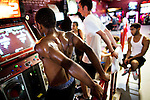 "NEW YORK  --  JULY 17, 2010:  Andre Scott (L), 20, of the LES; dances against Peter Kokolis (C), 19 of Queens; on the ""In The Groove 2"" dance video game at the Chinatown Fair Video Arcade on Mott Street in Chinatown on July 17, 2010 in New York City. Scott comes to the arcade 4 to 5 times a week, Kokolis comes about once a week. (PHOTOGRAPH BY MICHAEL NAGLE)"
