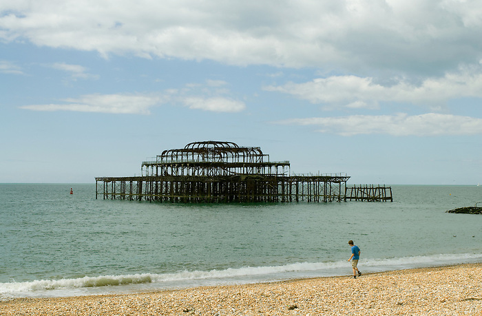 A boy at the water's edge on Brighton beach, with the derelict shell of the West Pier in the background.
