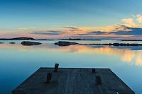 Brygga och spegelblankt vatten bland låga skär i ytterskärgården på Ut-Fredel iStockholms skärgård. / Outer Stockholms archipelago Sweden.