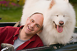 mature male with his husky dog in sports car