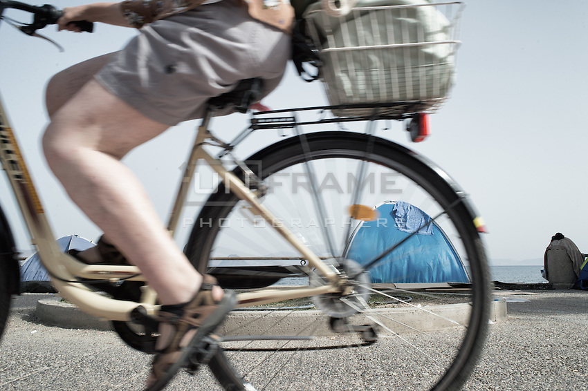 Tourist pedaling her bicycle past a makeshift refugee encampment. Kos, Greece. Sept. 7, 2015