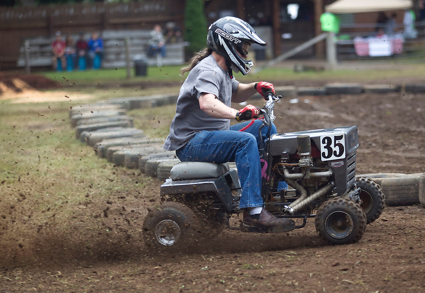 """Dirt flies as Keith Koopman takes a corner during a lawnmower race at the annual """"Territorial Days"""" festival in Amboy Sunday July 10, 2016. Other events during the celebration included a logging show, musical performances, an art show and a carnival. The celebration highlights the area's connection to logging and pioneering.  (Photo by Natalie Behring/ for the The Columbian)"""