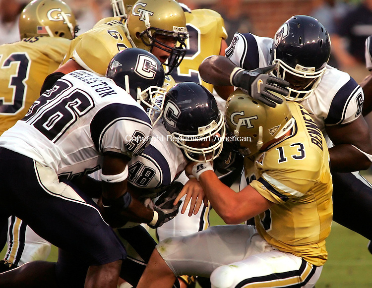 ATLANTA, GA--17 September 2005- 101705JS04--Georgia Tech quarterback Taylor Bennett (13) gets hauled down by UConn's Dahna Deleston (36), Danny Lansanah (48) and Dan Davis (6) during the first half of their game Saturday at Bobby Dodd Stadium in Atlanta, Georgia.   Jim Shannon / Republican American--UConn, Georgia Tech, Bobby Dodd Stadium, Atlanta, Georgia are CQ