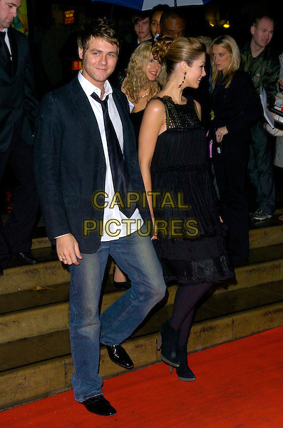 BRIAN McFADDEN & DELTA GOODREM.Arrivals - Emeralds & Ivy Ball, The Roundhouse, .London, England, December 1st 2006..full length black dress tights ankle boots tie white shirt jeans holding hands couple walking down steps.CAP/CAN.©Can Nguyen/Capital Pictures