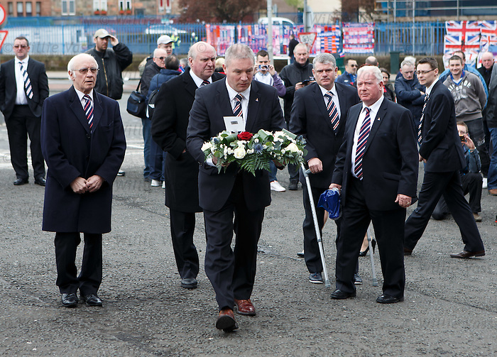 Rangers manager Ally McCoist lays a floral tribute in memory of Sandy Jardine at the Copland Road blue gates at Ibrox