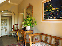 The cherrywood console table and bench in the entrance hall are both French and the contemporary painting is a view of San Sebastian