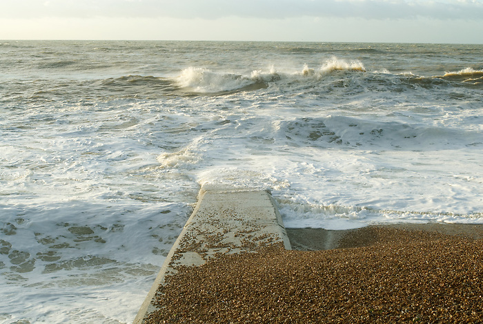 Stormy seas on the English coast wash shingle across the top of a groyne - a breakwater intended to check coastal erosion and longshore drift.