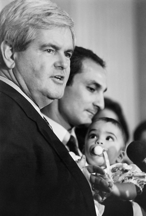 "Olivia Joseph (8 months) holding on to Speaker of the House Rep. Newton Leroy ""Newt"" Gingrich, R-Ga., as father Gabe tooks on.  Her father had just spoken about balancing budget and tax relief. (Photo by CQ Roll Call)"