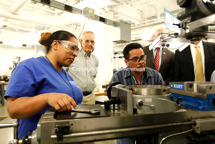 Waterbury, CT- 24 April 2014-042414CM01- Naugatuck Valley Community College manufacturing students, Priscilla Rodriguez, left, and Armando Rodriguez both from Waterbury, give a demonstration on a Bridgeport Vertical Milling machine at the college in Waterbury on Thursday.  Looking on is Ed Tremblay, treasurer with the local Precision Metalforming Association.  The college's Advanced Manufacturing Program received a grant from the Precision Manufacturing Association Educational Foundation.  The grant will help recruit future students into the program.    Christopher Massa Republican-American