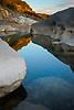 Limestone boulders on a calm Pedernales River at sundown, Pedernales Falls State Park, Texas, USA.