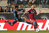 Sheanon Williams (25) of the Philadelphia Union goes for a tackle on Joel Lindpere (26) of the Chicago Fire. The Philadelphia Union defeated the Chicago Fire 1-0 during a Major League Soccer (MLS) match at PPL Park in Chester, PA, on May 18, 2013.