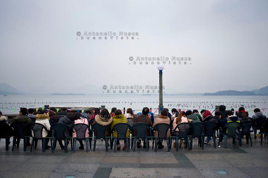 Gente seduta sul lungo lago al tramonto.<br /> People sitting on the terrace of West Lake in hangzhou