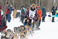 Robert Bundtzen and team run past spectators on the bike/ski trail near University Lake with an Iditarider in the basket and a handler during the Anchorage, Alaska ceremonial start on Saturday, March 7 during the 2020 Iditarod race. Photo © 2020 by Ed Bennett/Bennett Images LLC