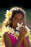 A pretty young local girl wearing a plumeria lei holds a plumeria blossom to her face.