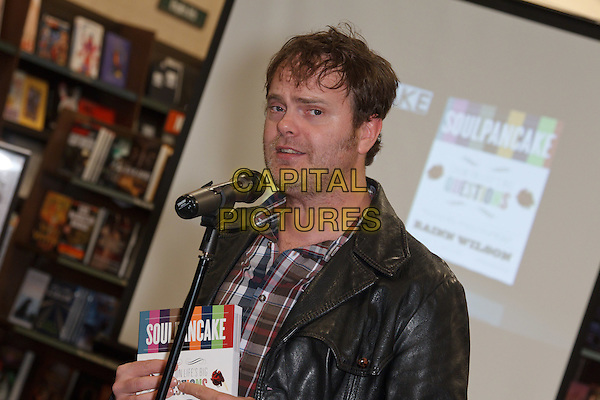 "RAINN WILSON.Rainn Wilson signs copies of his new book, ""Soul Pancake,"" at Barnes & Noble Huntington Beach, Huntington Beach, CA, USA. .November 18th, 2010.booksigning half length black leather microphone stubble facial hair .CAP/CEL.©CelPh/Capital Pictures."