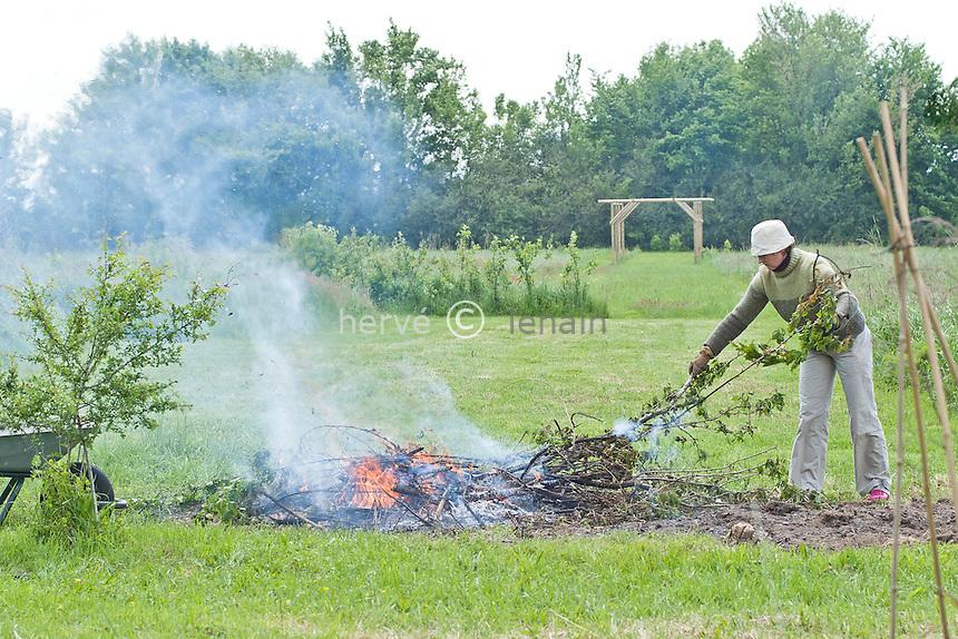 feu dans un jardin : brulage des branches et branchages issus des tailles // Fire in a garden for branches