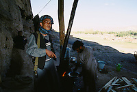 Local young Hazara Mujahedins of the Hezb e Wahdat Islami of Karim Kalili, cooking the evening meal and living in a cave of the cliff, left of the 54 meters Bamiyan Buddha.