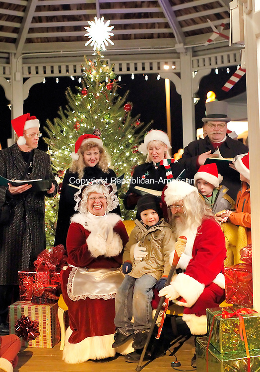 Harwinton, CT-03 December 2011-120311CM13-   Jacob Morin, 5, of Harwinton sits with Mr. and Mrs. Clause during the first annual Harwinton Hometown Celebration.  Behind them are Uncommon Time, who were singing Christmas tunes. The event, celebrated around the town hall and library, featured hay rides, photos with Santa, craft fair and bake sale.   Christopher Massa Republican-American