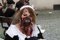 Woman dressed up to participate in the Zombie Walk in Prague in May 2014, wearing a black and white dress, and with scars in her face.