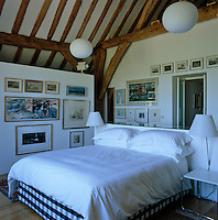 This double bedroom is decorated with a collection of framed prints and paintings
