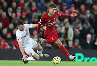 2nd January 2020; Anfield, Liverpool, Merseyside, England; English Premier League Football, Liverpool versus Sheffield United; Roberto Firmino of Liverpool evades a tackle from John Fleck of Sheffield United - Strictly Editorial Use Only. No use with unauthorized audio, video, data, fixture lists, club/league logos or 'live' services. Online in-match use limited to 120 images, no video emulation. No use in betting, games or single club/league/player publications
