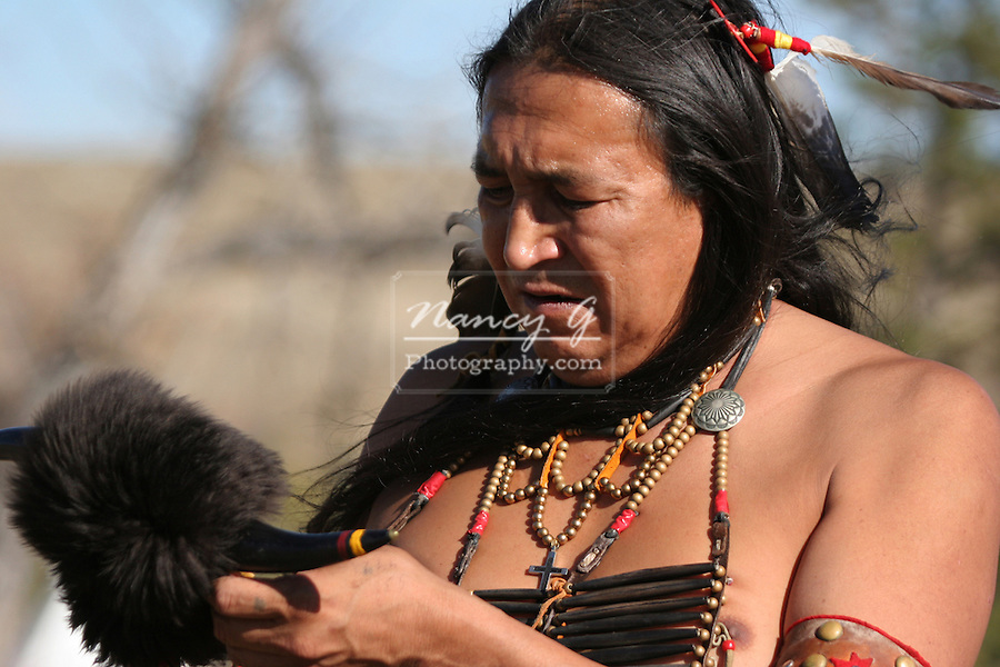A Native American Indian man looking at his horned club weapon