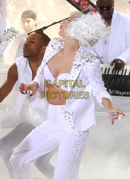 """LADY GAGA (Stefani Joanne Angelina Germanotta) .performs live on NBC's """"TODAY"""" Show at Rockefeller Center, New York, NY, USA, 9th July 2010..on stage music concert gig half length white microphone funny dancing profile cross suit jacket bra feather lace ear muffs head band hair hairband silver beaded studded embellished hand .CAP/ADM/AC.©Alex Cole/AdMedia/Capital Pictures."""