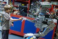 Quebec city, August 1, 2008 - Louis Prevost-Bolduc, 9, shakes hand with a man-size robot at Benjo toy store on St-Joseph street in Quebec city. Benjo is a 28,000-square-foot game and toy store filled with dolls, teddy bears, crafts, candy, model trains and cars, and more.