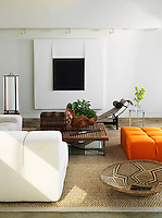 Contemporary furniture is arranged on a sisal rug in the open-plan living room which has a large black and white artwork on the wall