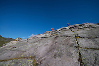 Two hikers ascend rock slabs on way to Peak 492, Moskenesøy, Lofoten Islands, Norway